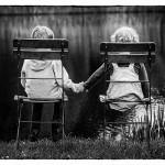 Geschwister sitzen am See auf Stühlen